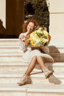 Schöne frau des smileys draußen mit blumenstrauß der frühlingsblumen