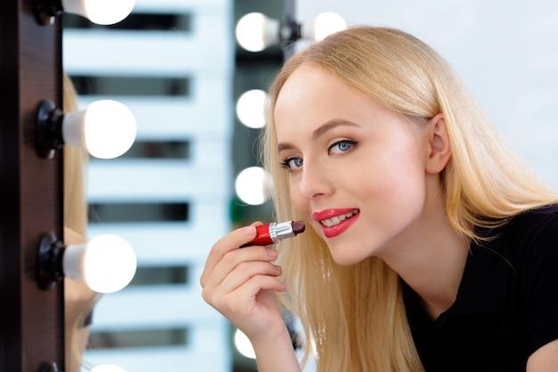 Schöne frau, die abend make-up tut