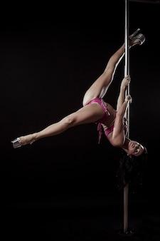 Schöne frau, die akrobatische und flexible tricks auf stange im tanzstudio tut