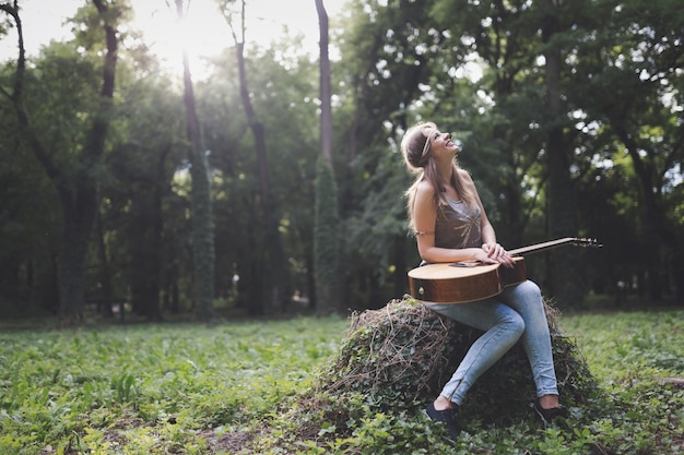 Schöne frau, die akustikgitarre in der natur spielt