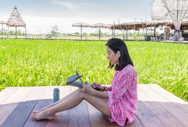 Schöne frau, die am laptop sitzt auf holzterrasse im freien arbeitet