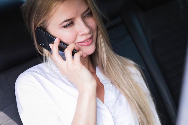Schöne frau, die am telefon auf dem rücksitz des autos spricht