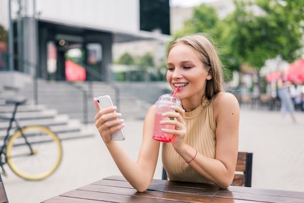 Schöne frau, die am telefon chattet, über skype spricht und einen cocktail trinkt, in einem café auf der straße sitzt sitting