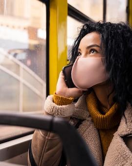 Schöne frau, die am telefon im bus spricht