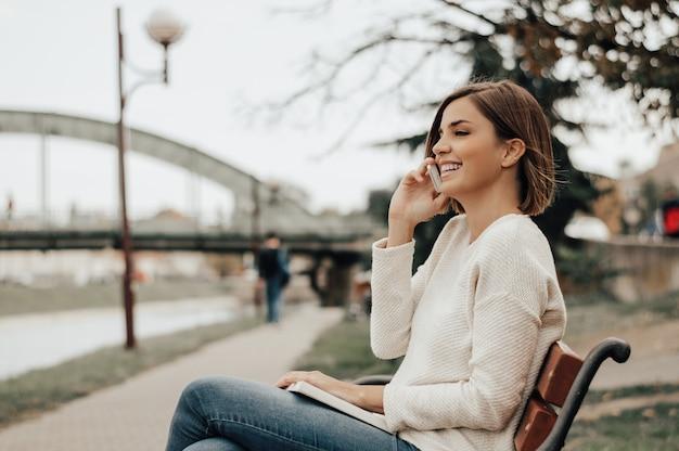 Schöne frau, die am telefon im stadtpark spricht.