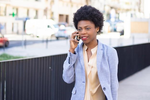 Schöne frau, die am telefon während des spaziergangs spricht