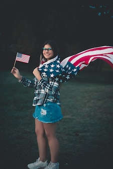 Schöne frau, die amerikanische flagge - bild anhält