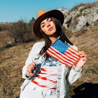 Schöne frau, die amerikanische flagge in der natur hält