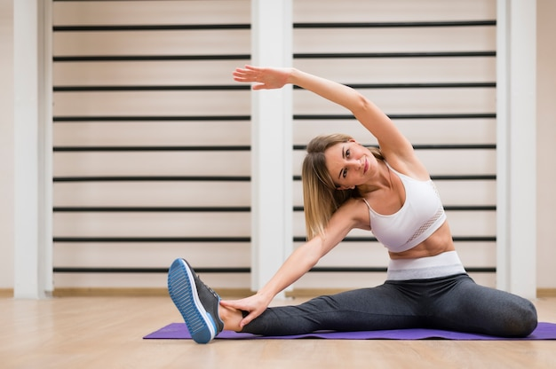 Schöne frau, die an der gymnastik trainiert