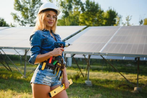 Schöne frau, die an der installation von sonnenkollektoren arbeitet