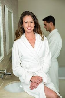 Schöne frau, die an der kamera im badezimmer lächelt