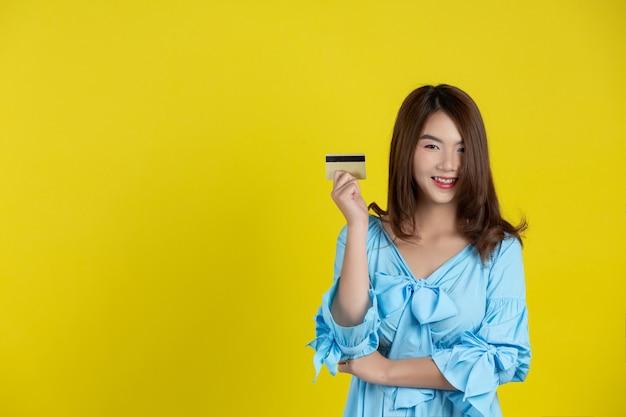Schöne frau, die an der kamera lächelt und kreditkarte auf gelber wand hält