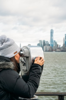 Schöne frau, die an einem bewölkten tag durch ein teleskop auf new york city schaut - vertikales bild