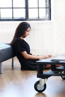Schöne frau, die an ihrem laptop arbeitet