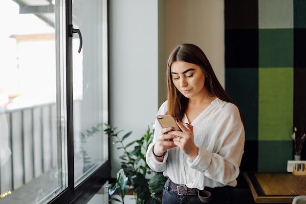 Schöne frau, die an ihrem laptop und telefon an einem stilvollen städtischen restaurant arbeitet