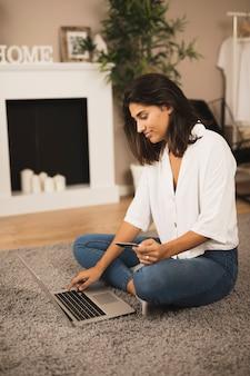 Schöne frau, die an laptop arbeitet