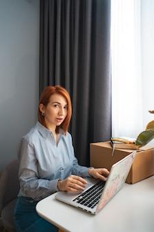 Schöne frau, die an laptop im mitarbeitsbereich arbeitet