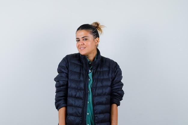Schöne frau, die anmutig lächelt, während sie in grünem hemd, schwarzer jacke posiert und glücklich aussieht. vorderansicht.