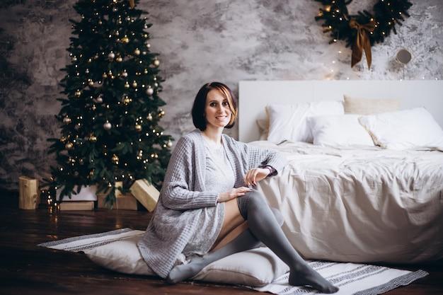 Schöne frau, die auf bett am weihnachten sich entspannt