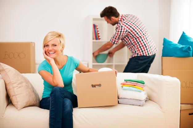 Schöne frau, die auf couch ruht, während ihr ehemann ihr neues wohnzimmer verziert