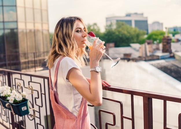 Schöne frau, die auf dem balkon mit cocktail am junggesellinnenabschied steht. danke schön. sie trinkt