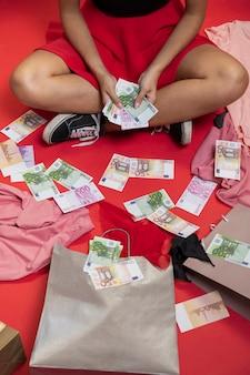 Schöne frau, die auf dem boden mit geld sitzt