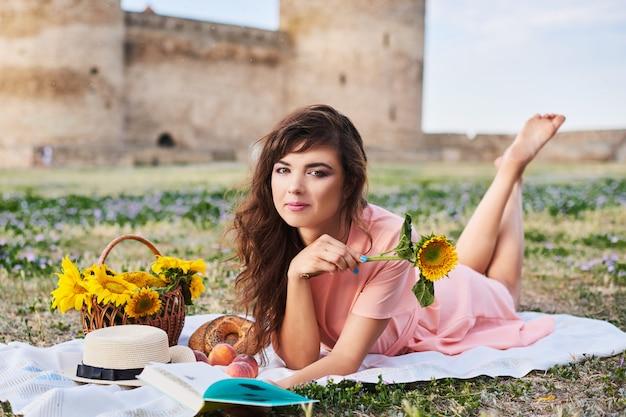 Schöne frau, die auf dem gras liegt. picknick gegen mittelalterliche burg