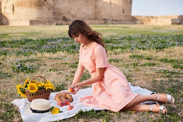 Schöne frau, die auf dem gras sitzt. picknick gegen mittelalterliche burg