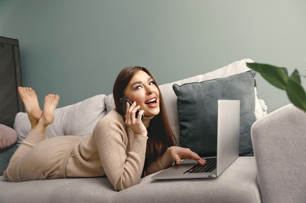 Schöne frau, die auf dem handy spricht, während sie den laptop für die fernarbeit verwendet