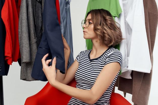 Schöne frau, die auf dem roten stuhl in der nähe der garderobengefühle sitzt