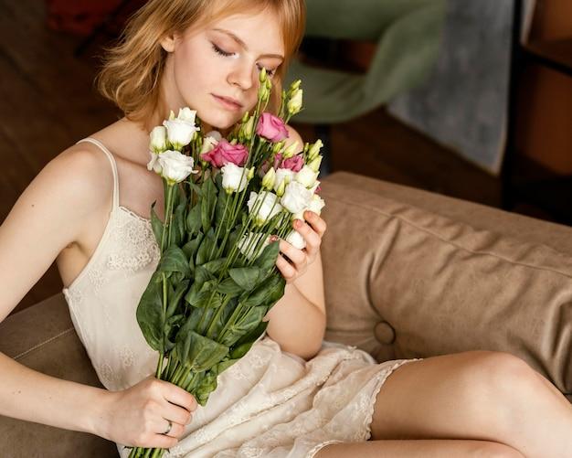 Schöne frau, die auf dem sofa beim halten des straußes der zarten frühlingsblumen aufwirft