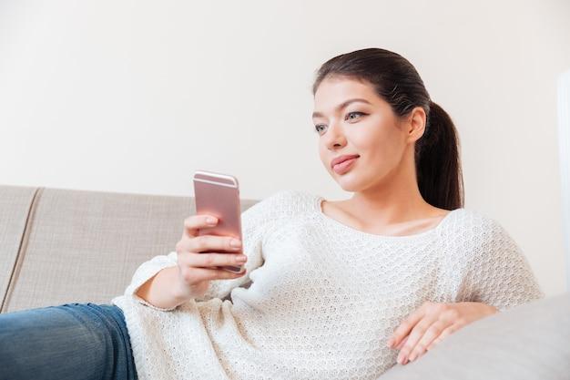 Schöne frau, die auf dem sofa liegt und zu hause smartphone benutzt