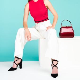 Schöne frau, die auf der bank mit roter handtaschengeldbörse und schuhen mit hohen absätzen sitzt.