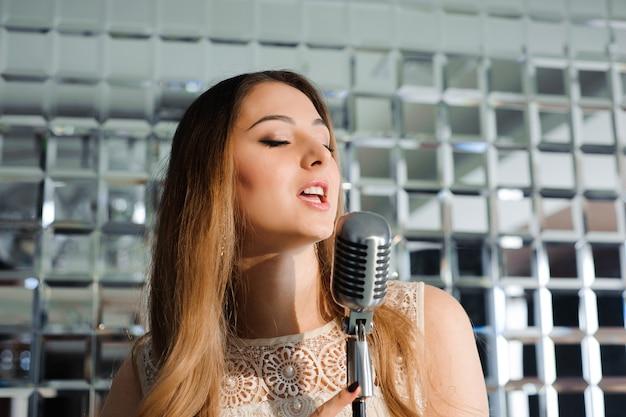 Schöne frau, die auf der bühne neben dem mikrofon singt.