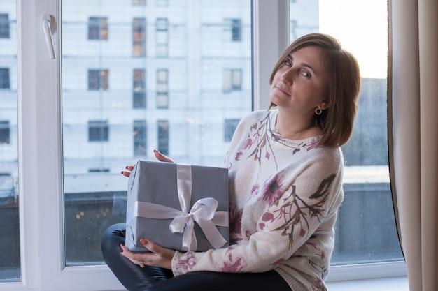 Schöne frau, die auf der fensterbank eines panoramafensters mit geschenk zu hause sitzt.