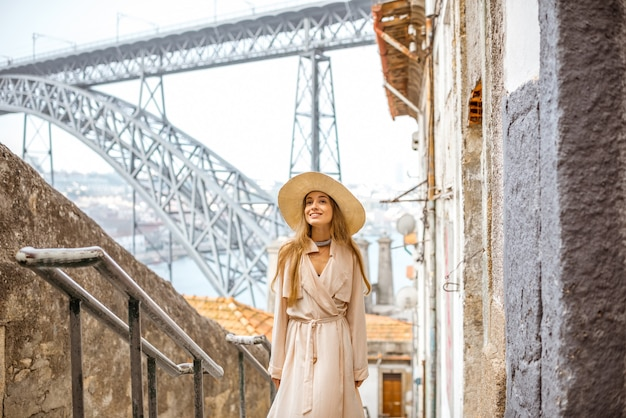 Schöne frau, die auf der treppe mit der berühmten eisenbrücke auf dem hintergrund in der stadt porto, portugal geht