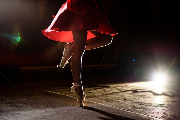Schöne frau, die auf einem schwarzen hintergrund tanzt.