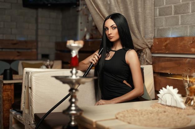 Schöne frau, die auf einem sofa sitzt und eine wasserpfeife raucht