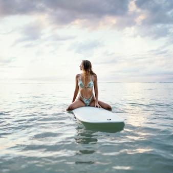 Schöne frau, die auf einem surfbrett im wasser sitzt