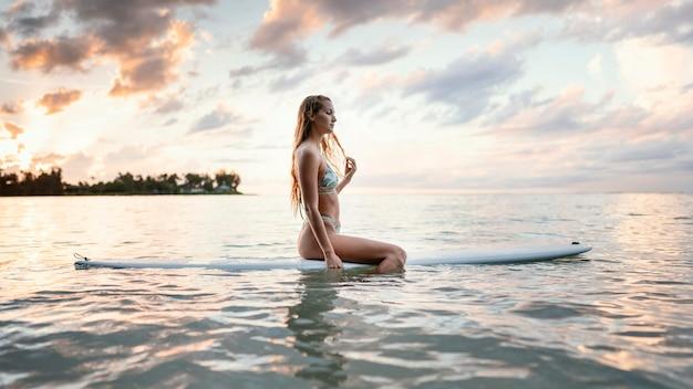 Schöne frau, die auf einem surfbrett sitzt