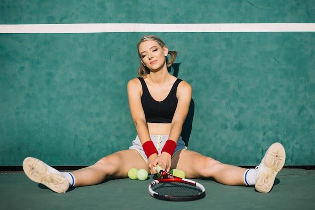 Schöne frau, die auf einem tennisfeld sitzt