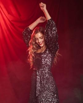 Schöne frau, die auf einen roten vorhanghintergrund lächelt und tanzt