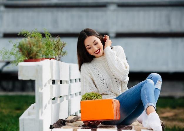 Schöne frau, die auf einer bank sitzt und in ihren händen ein geschenk hält