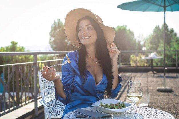 Schöne frau, die auf einer terrasse zu mittag isst