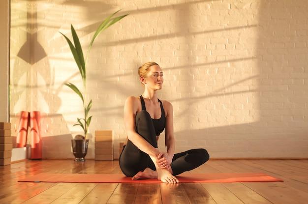 Schöne frau, die auf einer yogamatte in einem studio sitzt