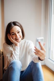 Schöne frau, die auf fensterbank lacht und selfie am telefon nimmt