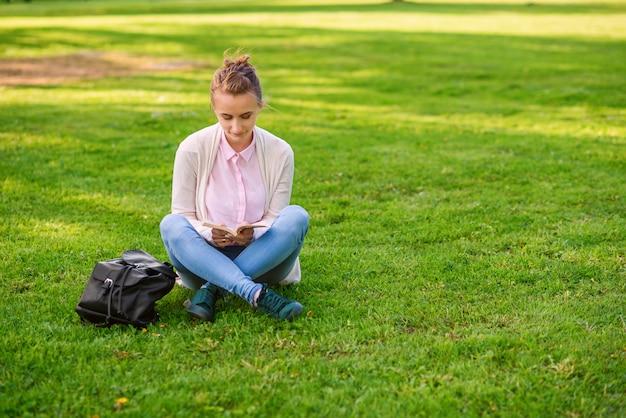 Schöne frau, die auf gras sitzt und buch im park im sommer liest