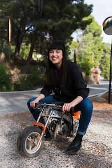 Schöne frau, die auf kleinem motorrad sitzt
