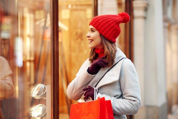 Schöne frau, die auf schaufenster während des wintereinkaufs schaut