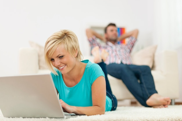 Schöne frau, die auf teppich liegt und laptop verwendet